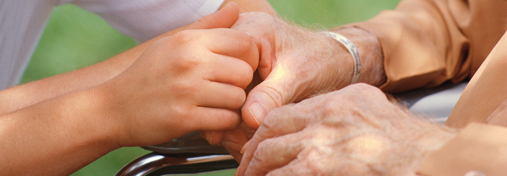 Child's hand clasping elderly hand