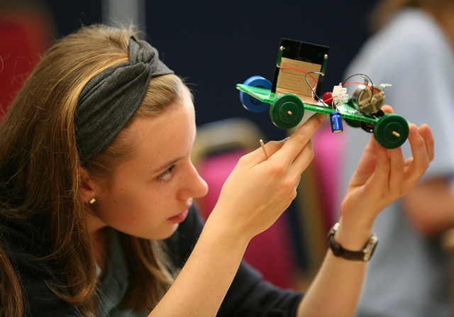 female student examines solar-powered model car