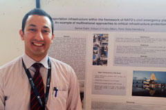 A graduate student in front of his  poster