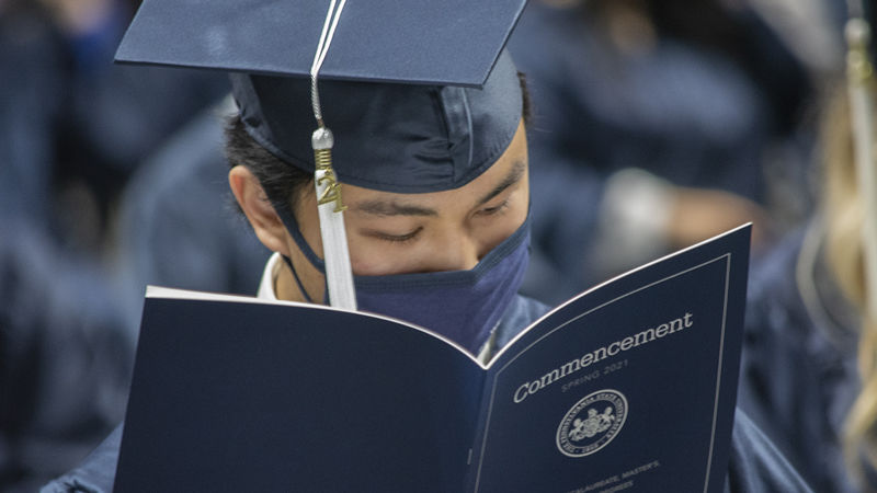graduate in cap and gown reading commencement program