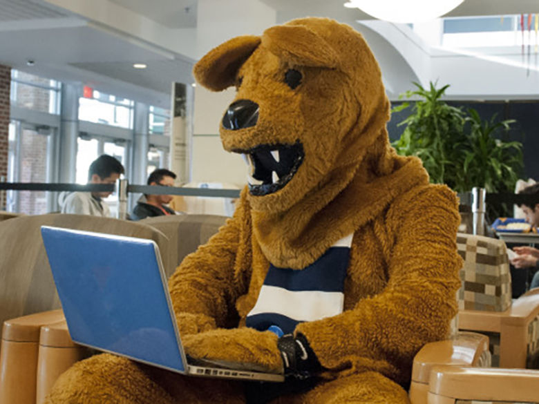 Nittany Lion using a laptop in the Library