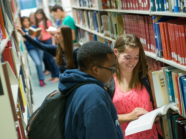 students work together among library bookshelves
