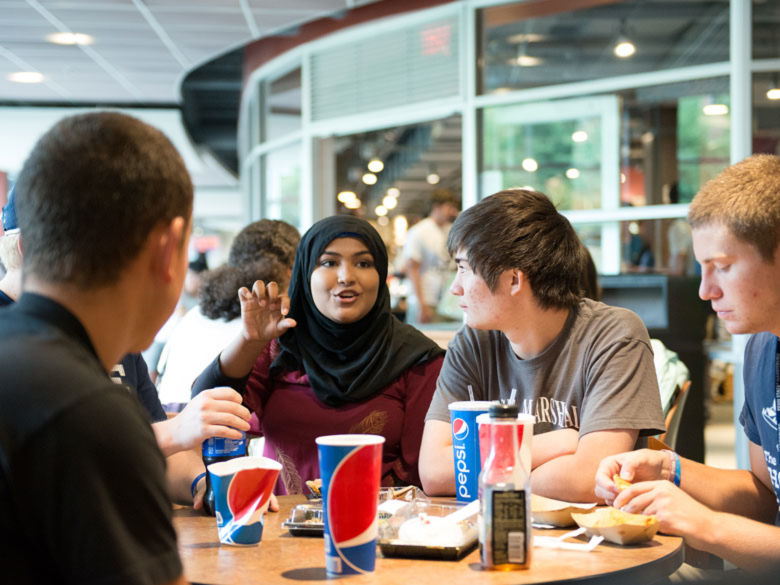 students eating and talking in the dining hall