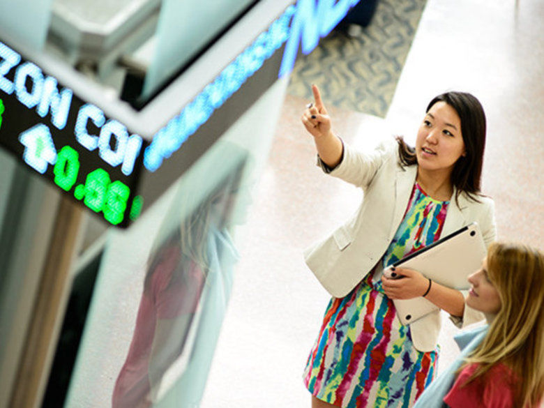 two business women looking at a digital signage