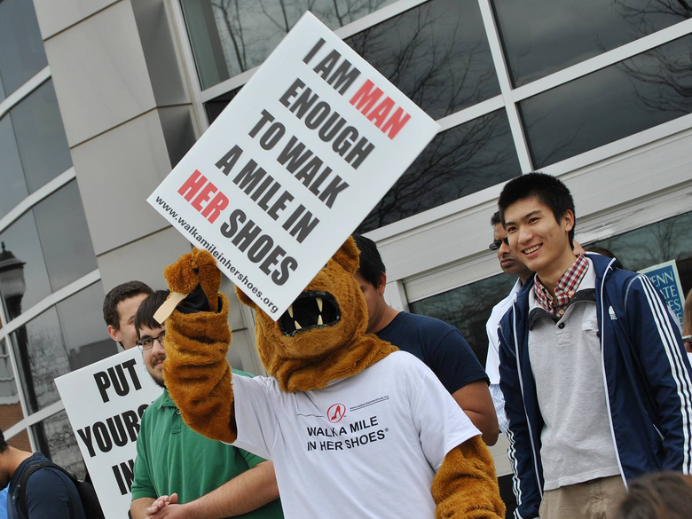 The Nittany Lion mascot holding a Walk A Mile in Her Shoes sign