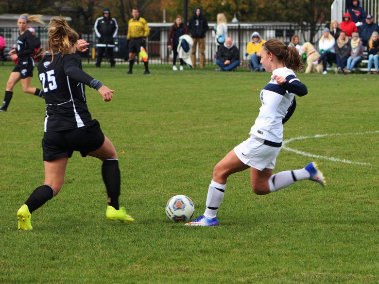 women's soccer player battling for possession