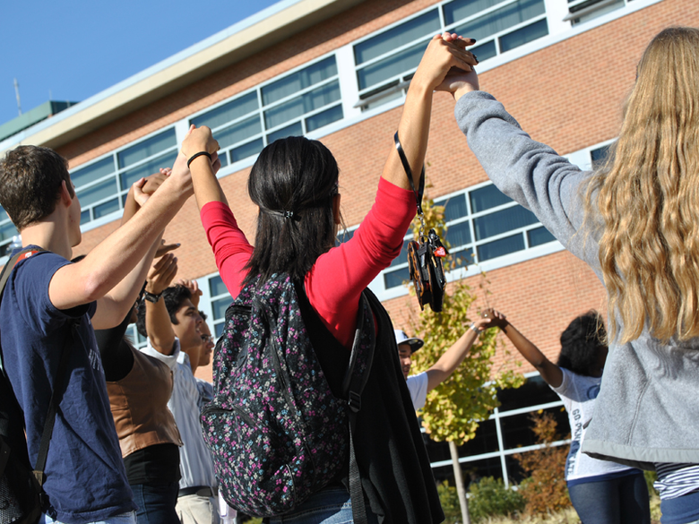 college students of various ethnicities holding hands as a sign of diversity and unity