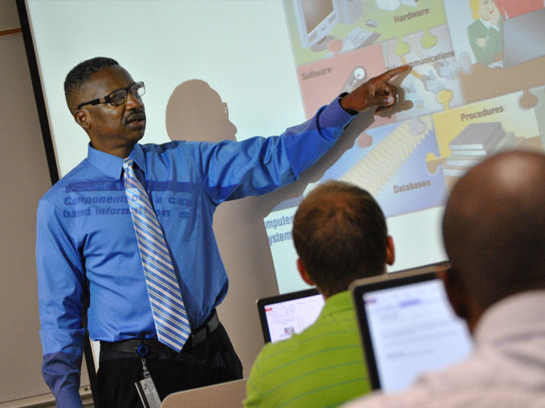 Professor lecturing and pointing to a presentation on screen