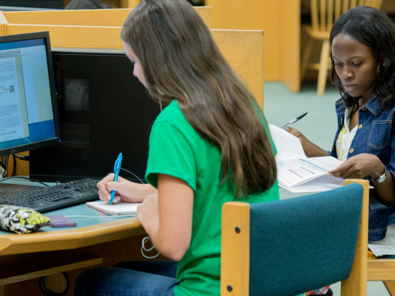 Two female students studying and taking notes in the library