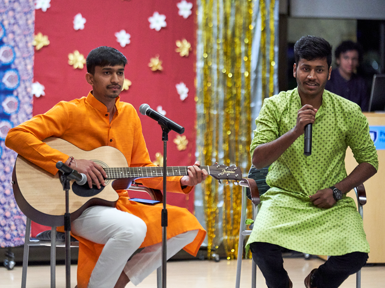 Two international students perform at Diwali, playing guitar and singing