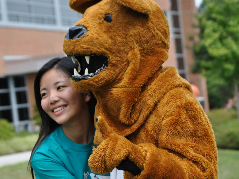 A female college student hugging the Nittany Lion mascot