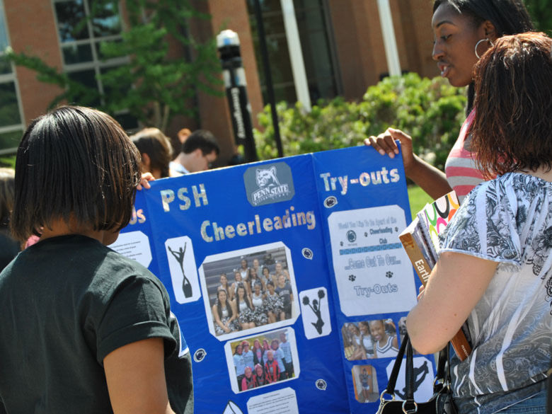 students promoting the cheerleading club at the club fair