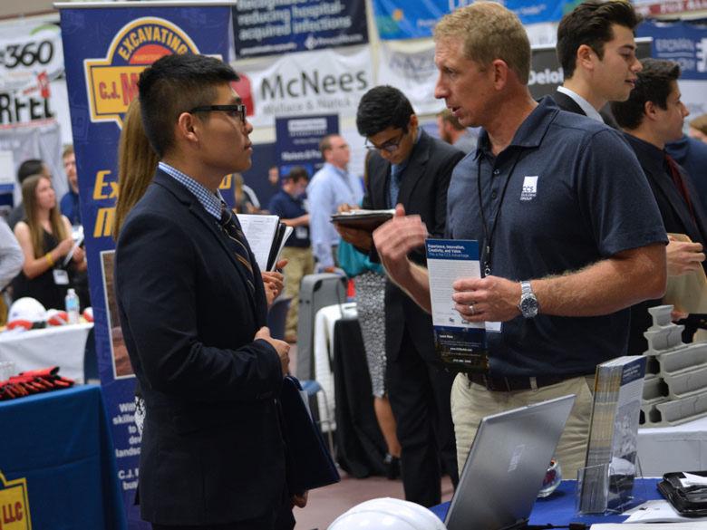 student talks to a recruiter at a job fair