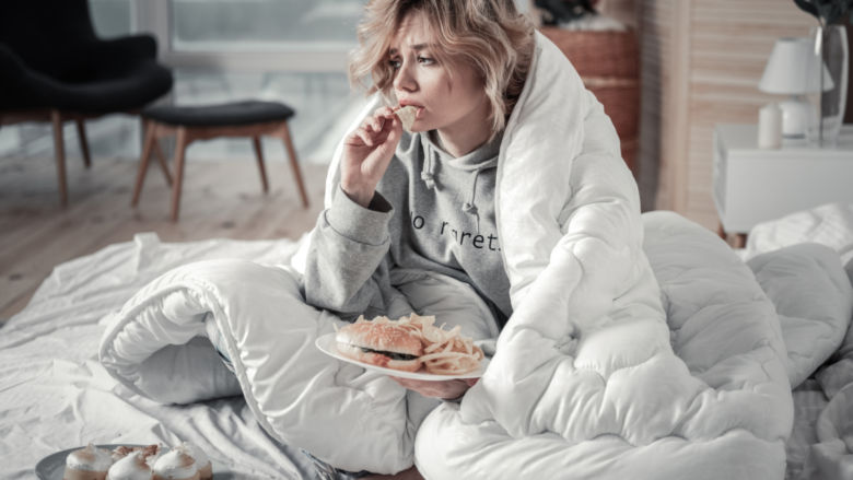 A woman eating ice cream looking sad and wrapped up in a blanket
