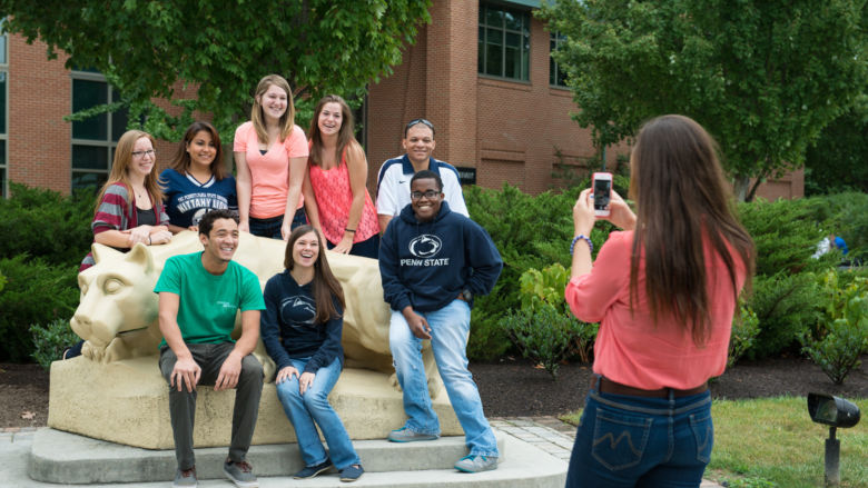 students pose for a photo in front of Penn State Harrisburg's Lion Shrine and Library