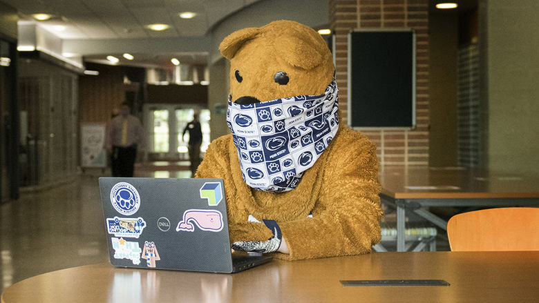 The Nittany Lion using a laptop while wearing a mask.