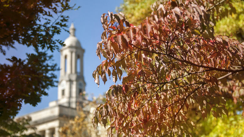 Old Main bell tower with autumn leaves in foreground
