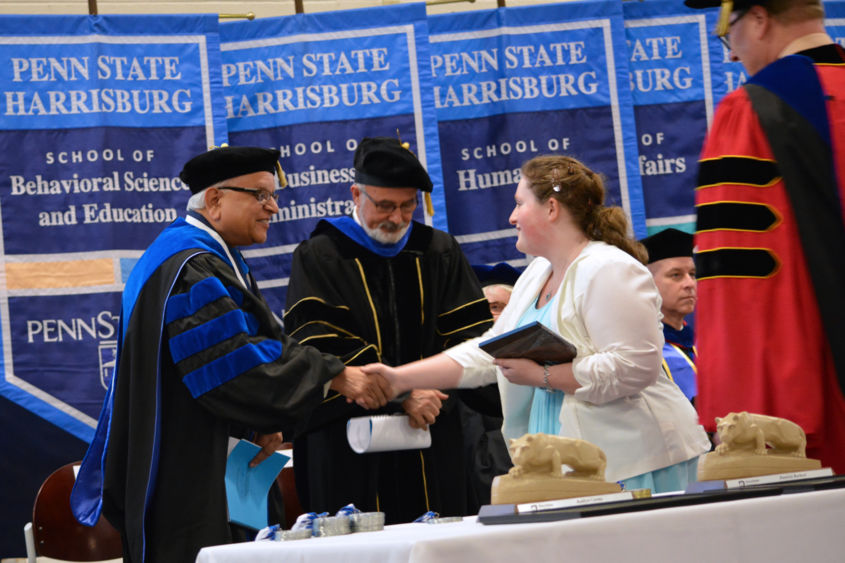 Drs. Mukund Kulkarni and Omid Ansary congratulate Catharine Pinkerton on her award.