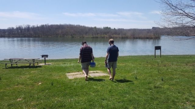 Two people facing out looking at a lake