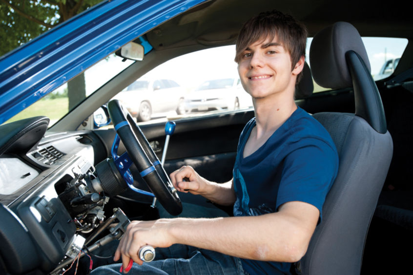 Steven Georges behind the wheel of his manual-transmission Honda, with a hand-operated clutch system he helped design.